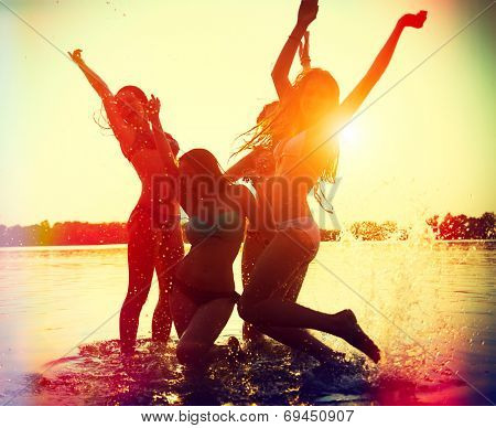 Beach Party. Teenage girls having fun in water. Group of happy young people dancing at the beach on beautiful summer sunset. Silhouettes of group of teen girls jumping and dancing. Joyful friends