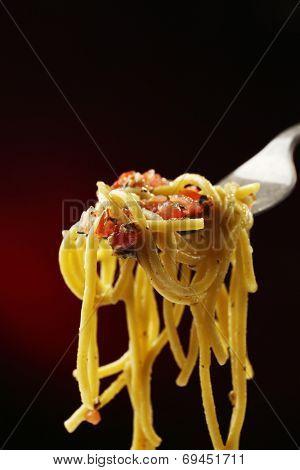 Italian pasta spaghetti on fork on dark background