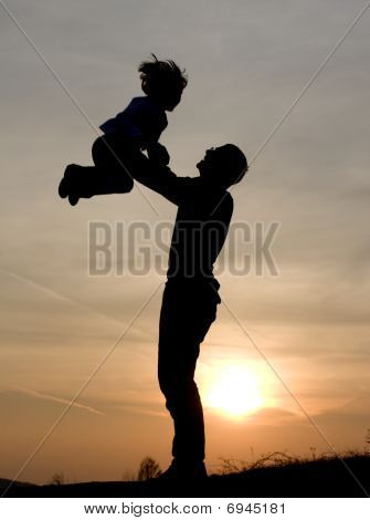 fun of father and child in sunset - silhouette