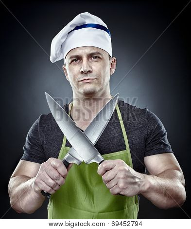Menacing Man Cook Holding Two Sharp Knives