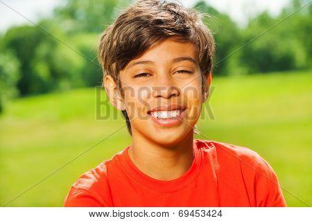 Brunet smiling boy in red T-shirt portrait