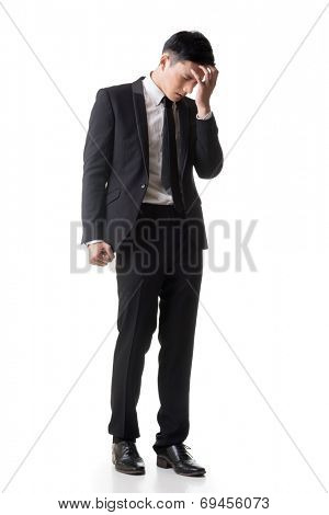 Regret young business man standing and thinking, full length portrait isolated on white background.