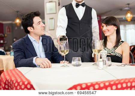 Waiter pouring wine to a couple