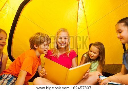 Five kids read books in a tent