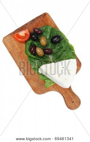 roquefort cheese on wooden platter with olives and tomato isolated over white background