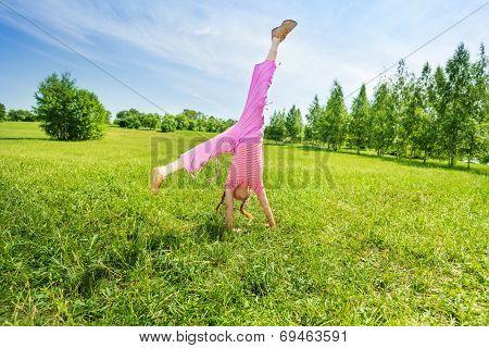 Active girl making flip on grass outside
