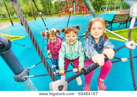 Three happy girls try climbing the grid