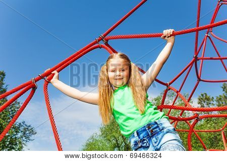 Girl with straight hands holds red rope of net