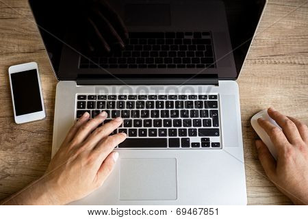 Male hands working on laptop, top view