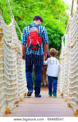 Father And Son Travelling By Suspension Bridge