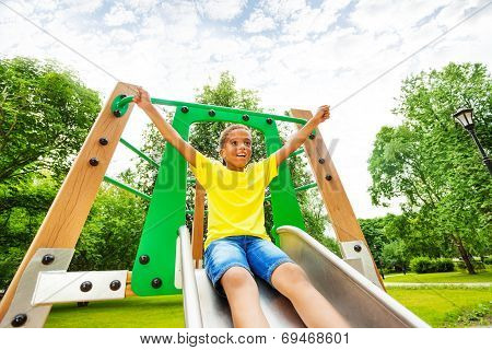 Excited boy with hands up on children chute