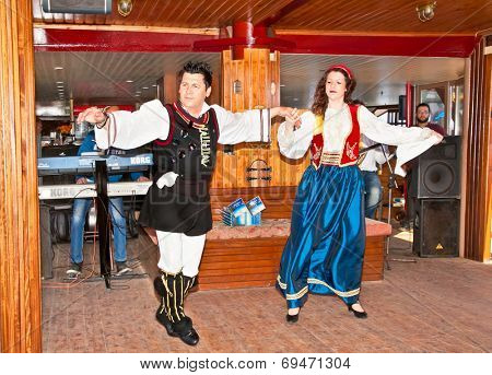 HAKIDIKI, GREECE-MAY 25, 2014: Greek folk music and dancing with traditional costume entertained tourists in Pirate ship, Greece on May 25, 2014.Pirate ship transport tourists around holy Athos,Greece