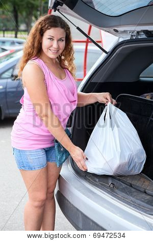 Woman Shopper Loading Bag In Trunk Of Her Suv