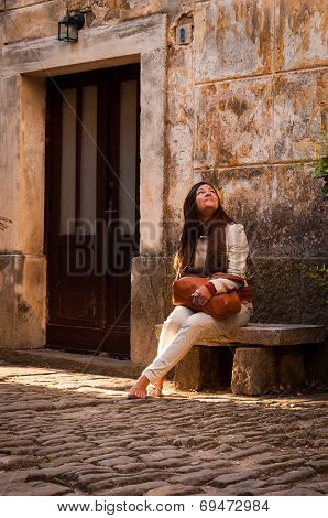 A Cute Woman Sitting On A Stone Bench In An Old Mediterranean Street