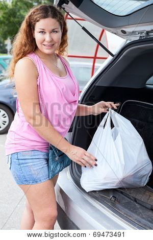 Attractive Young Woman Near Own Car With Shopping Bag