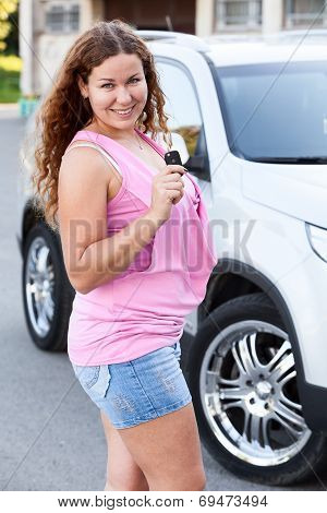 Woman In Pink Clothes Standing In Front Of Car With Ignition Key