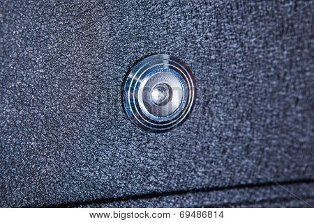 Silver peephole in  black iron door