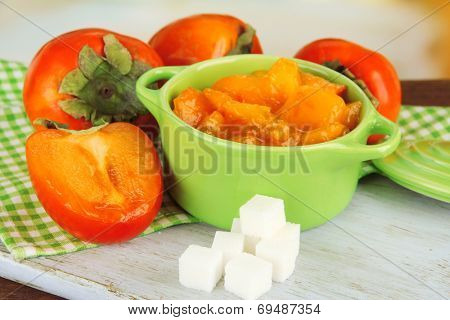 Ripe persimmons with jam in pot and sugar on table on bright background