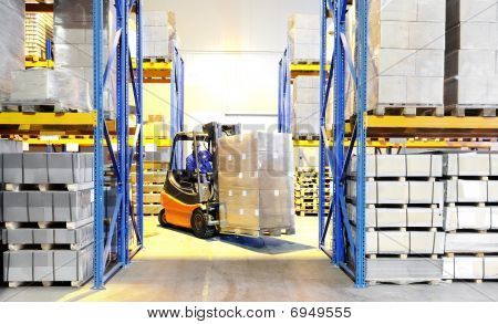 Forklift Loader And Worker At Warehouse