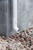 pic of downspouts  - Wall of building with white metall downspout and pavement