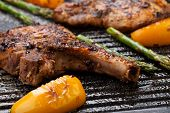 pic of pork chop  - Juicy pork chops are grilled on griddle with asparagus and bell pepper - JPG