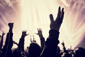 stock photo of clubbing  - Grunge style photo of silhouette of people hands raised up on musical concert - JPG