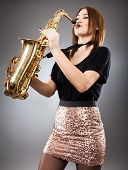 stock photo of saxophone player  - Beautiful blond woman saxophone player studio closeup shot - JPG