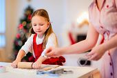 stock photo of cookie  - Family of mother and daughter baking gingerbread cookies at home on Christmas eve - JPG