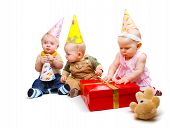 stock photo of party hats  - Three lovely toddlers in the party hats - JPG