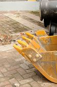 stock photo of hoe  - A back hoe bucket resting on a brick sidewalk scattered with debris - JPG