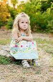 stock photo of pain-tree  - cute little girl for a walk upset sitting on a tree stump - JPG
