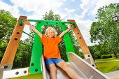 foto of chute  - Boy slides on playground chute with hands up - JPG