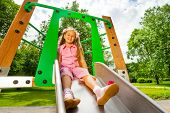image of chute  - Pretty small girl on playground chute sitting and smiling in the park - JPG