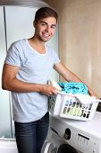 picture of dirty-laundry  - Man with basket of laundry - JPG