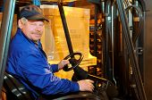 foto of lift truck  - Worker driver of a forklift loader in blue work wear at warehouse - JPG