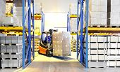 stock photo of forklift driver  - Worker driver of a forklift loader in blue workwear at warehouse with cardboard boxes on pallet - JPG