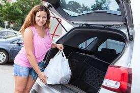 foto of pov  - Pretty woman holding bag with food neaar trunk of pov - JPG