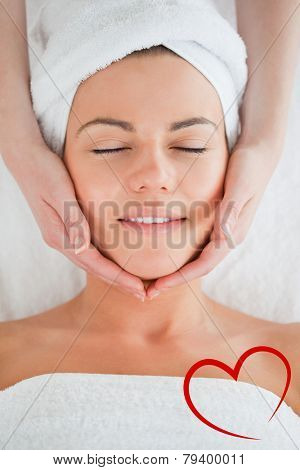 Portrait of a smiling woman having a facial massage against heart