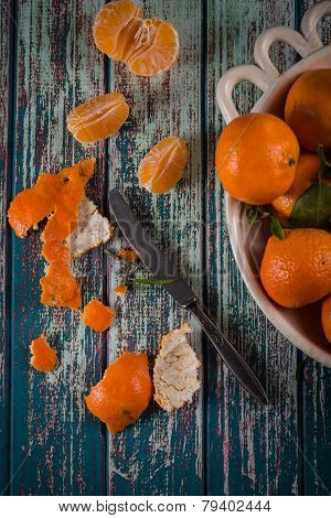 Peeling Freshly Picked Clementines With Knife On Rustic Table