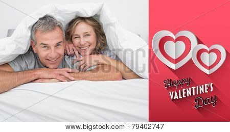 Cheerful couple under the duvet against happy valentines day