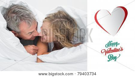 Loving middle aged couple under the duvet against happy valentines day