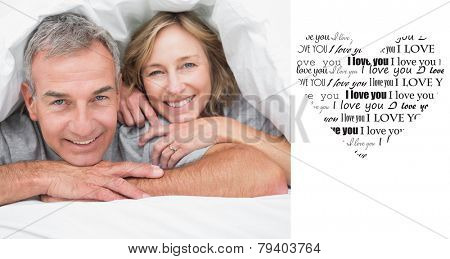 Loving couple under the duvet against valentines day pattern