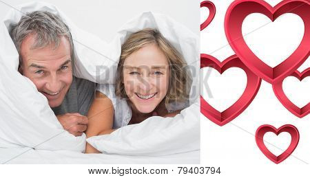 Happy middle aged couple under the duvet against pink hearts