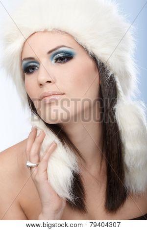 Portrait of seductive winter beauty in white fur cap.