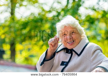 An Elderly Woman Of 80 Years Shows A Fig