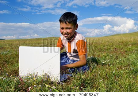 Mongolian boy with laptop on grass.