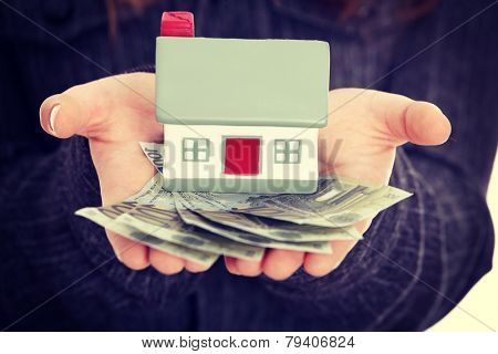 Beautiful young businesswoman holding euros bills and house model over white - real estate loan concept