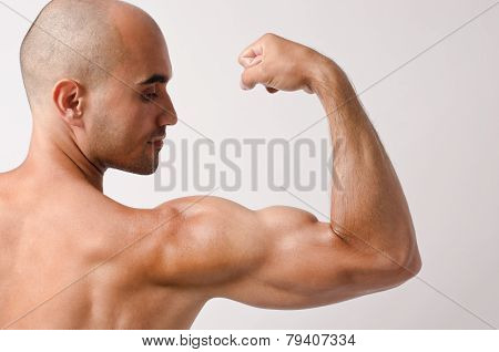 Topless fit man posing with his arm up showing his biceps.