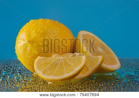Lemons in water drops on a blue background