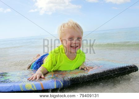Young Child Riding On Boogie Board In Ocean
